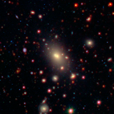 a picture of a galaxy cluster observed by the WISE and Spitzer Space Telescopes. The bright galaxy at the center is the BCG.