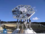 AMiBA on Mauna Loa, Hawaii in September 2006. Seven 60-cm antennas, covered with GoreTex sun protection shields, form the most compact configuration on the carbon fiber platform. An optical telescope, the correlator, associated mechanical and electronic p
